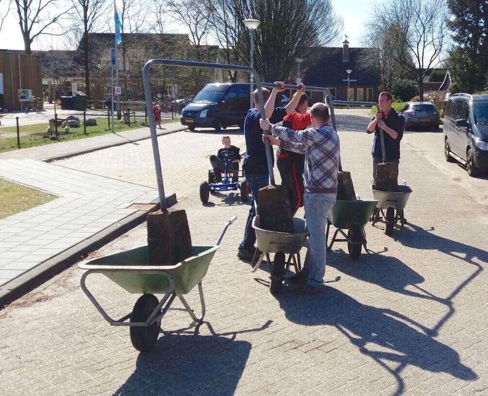 Vrijwilligers verplaatsen een klimrek bij MFA De Schans